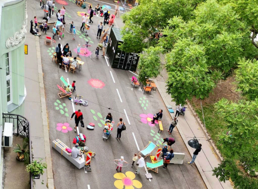 A leafy green city street with colourful chalk drawings on the floor